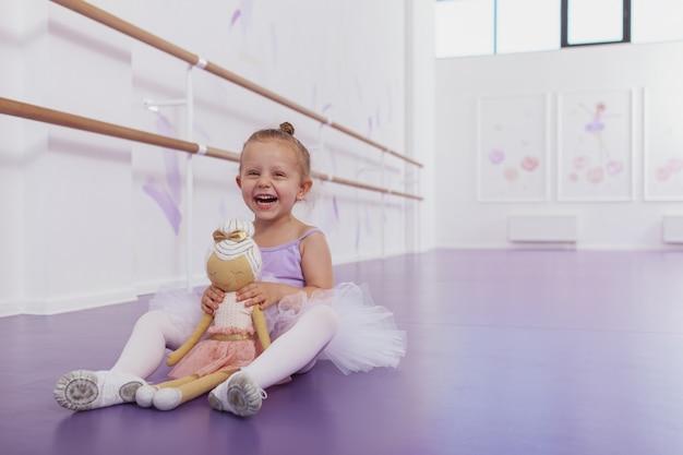 Heureuse mignonne petite fille ballerine rire joyeusement, assis sur le sol à l'école de ballet