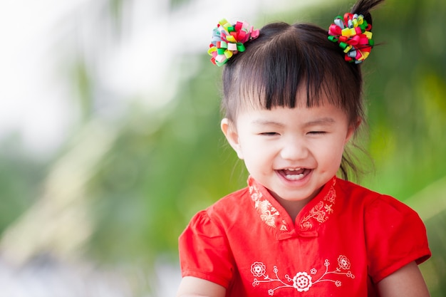 Heureuse mignonne petite fille enfant asiatique en robe chinoise tradition souriante