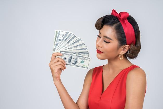 Heureuse mode main belle femme tenant l'argent du dollar