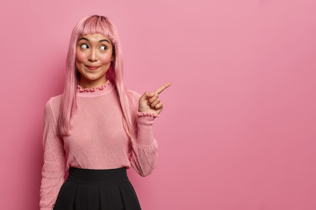 Heureuse mystérieuse femme orientale a les cheveux longs, pointe du doigt sur l'espace de copie, montre la place pour votre publicité, promeut la bannière de l'entreprise ou le produit