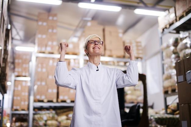Heureuse ouvrière d'usine célèbre le succès. intérieur de l'entrepôt.