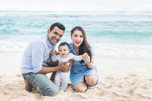Heureuse petite famille souriante pendant ses vacances sur la beac