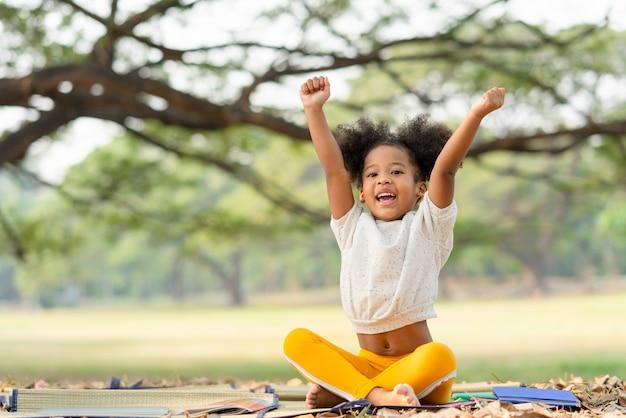 Heureuse petite fille afro-américaine souriant et lève la main tout en étant assis dans le parc