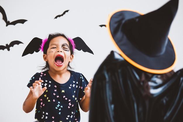 Heureuse petite fille asiatique en costumes et maquillage s'amuser sur la fête d'halloween