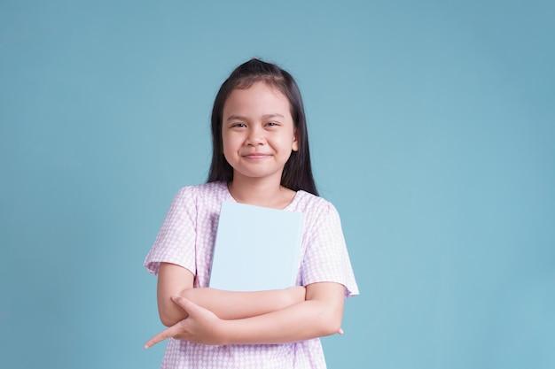 Heureuse petite fille asiatique debout tenant le livre