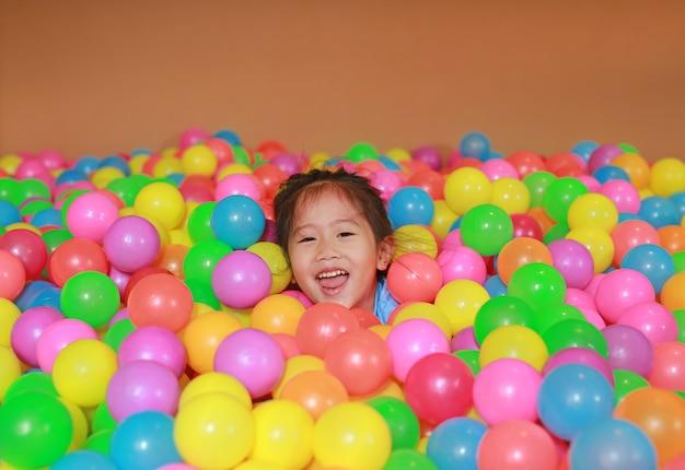 Heureuse petite fille asiatique jouant avec terrain de jeu de boules en plastique coloré.