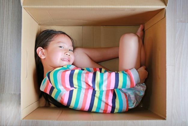 Heureuse petite fille asiatique joue et se trouvant dans une grande boîte en carton.