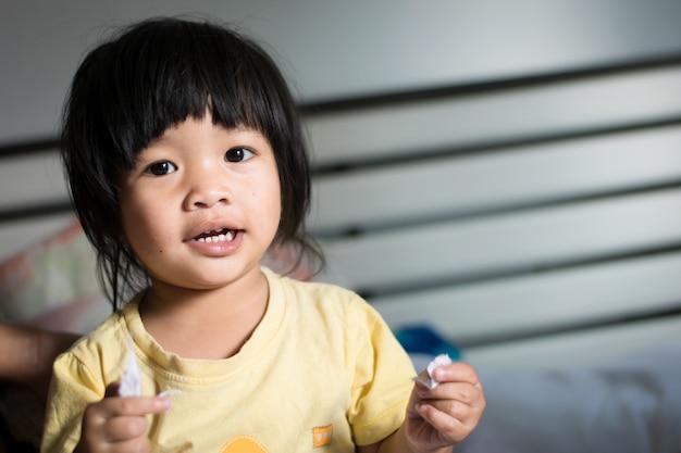 Heureuse petite fille asiatique sur le lit