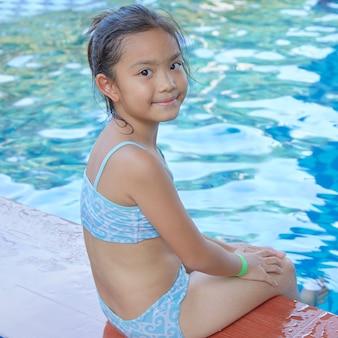 Heureuse petite fille asiatique à la piscine