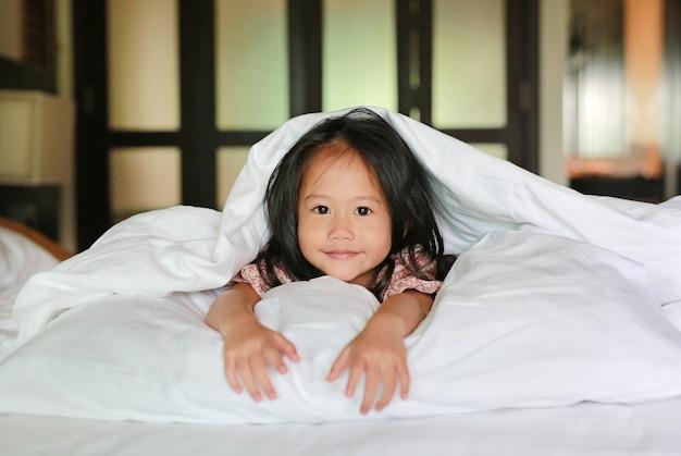 Heureuse petite fille asiatique en regardant la caméra avec couché sous la couverture sur le lit.