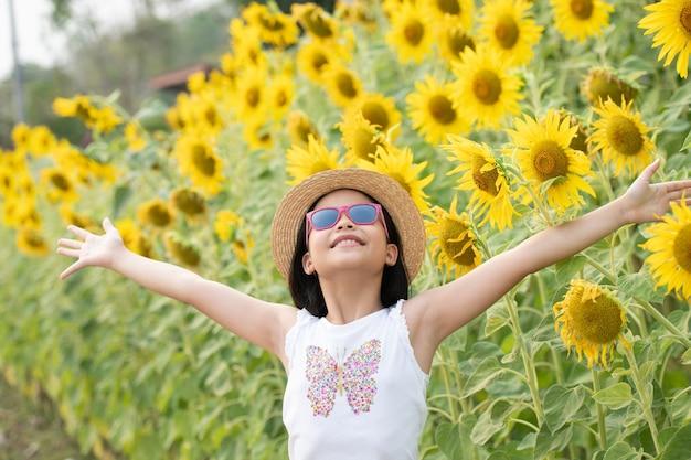 Heureuse petite fille asiatique s'amusant parmi les tournesols en fleurs sous les doux rayons du soleil.