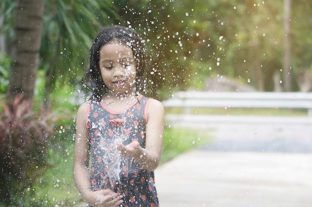 Heureuse petite fille asiatique s'amuser à jouer avec de l'eau dans un jardin avec espace de copie