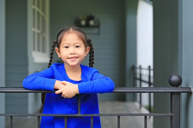 Heureuse petite fille asiatique se tenant au bar de la maison et à la recherche de caméra au matin.