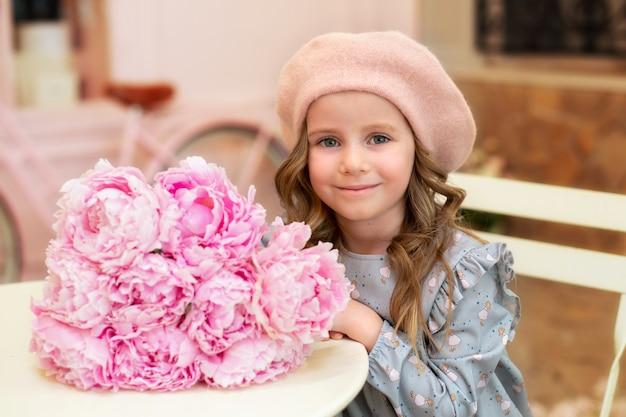 Heureuse petite fille aux cheveux bouclés en béret est assise à table avec bouquet de pivoines roses au café de la rue