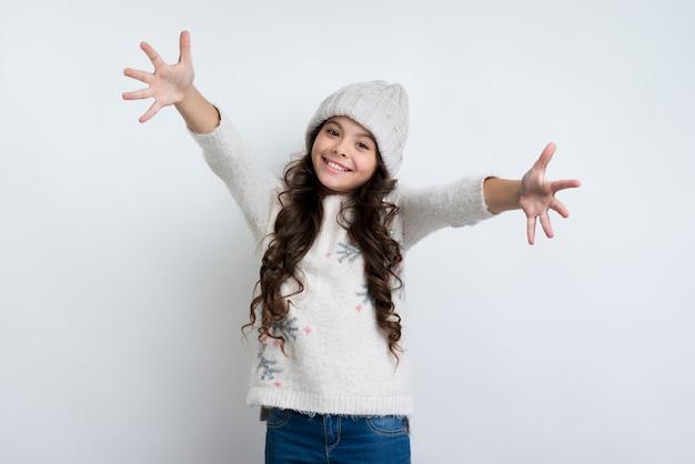 Heureuse petite fille aux mains tendues