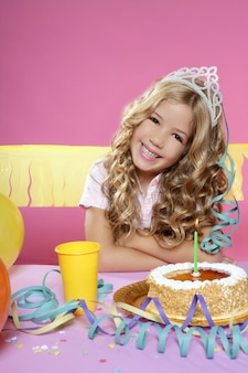 Heureuse petite fille blonde soufflant une bougie de gâteau dans une fête d'anniversaire