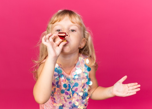 Heureuse petite fille blonde soufflant un sifflet de fête isolé sur un mur rose avec un espace de copie
