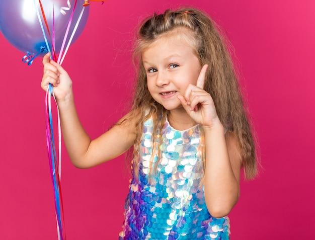 Heureuse petite fille blonde tenant des ballons à l'hélium et pointant vers le haut isolé sur un mur rose avec espace de copie