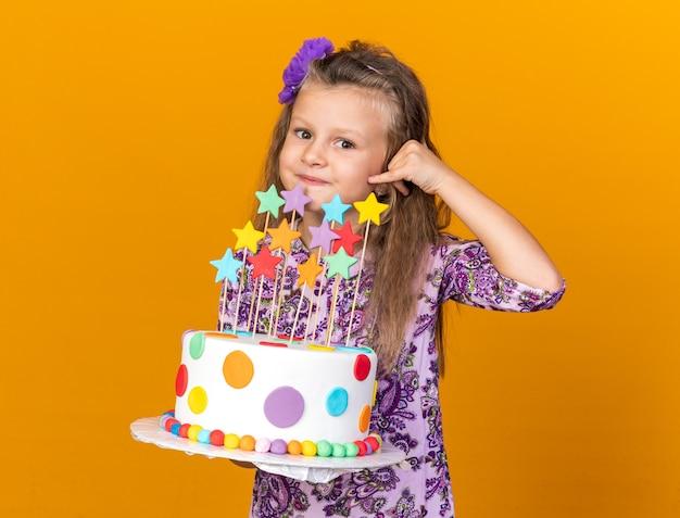 Heureuse petite fille blonde tenant un gâteau d'anniversaire et gesticulant un indicatif d'appel isolé sur un mur orange avec espace pour copie
