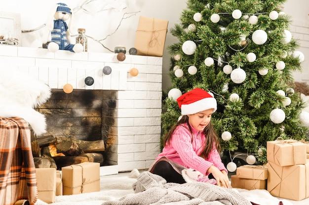 Heureuse petite fille avec cadeau de noël pose près du feu devant l'arbre de noël