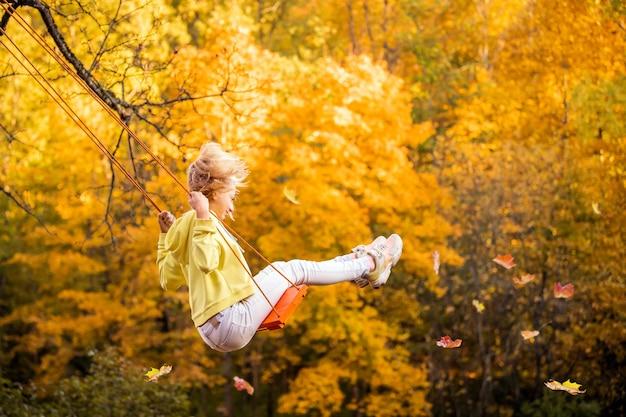 Heureuse petite fille caucasienne blonde souriante et chevauchant une balançoire en automne dans le parc.