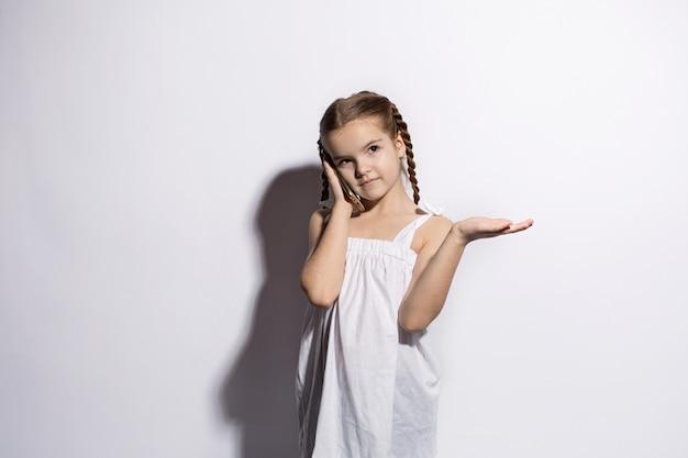 Heureuse petite fille caucasienne parler au téléphone sur fond blanc