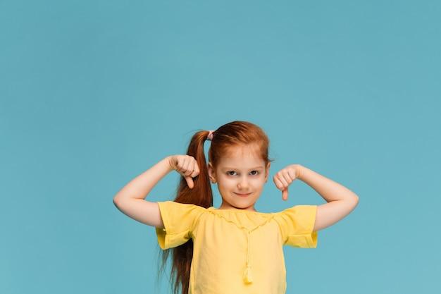 Heureuse petite fille caucasienne souriante en studio