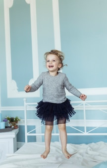 Heureuse petite fille de cinq ans sautant sur le lit