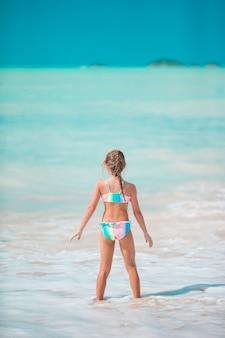 Heureuse petite fille courir et éclabousser à l'eau peu profonde à la plage