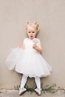 Heureuse petite fille dans une robe blanche avec un bonbon dans ses mains sur un mur gris