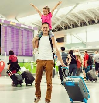 Heureuse petite fille embrassant son père dans le salon de l'aéroport après son arrivée avec sa mère