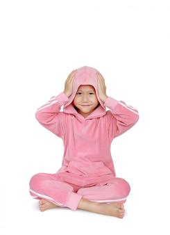 Heureuse petite fille enfant asiatique en tissu sport rose avec les mains touchant le capot sur la tête