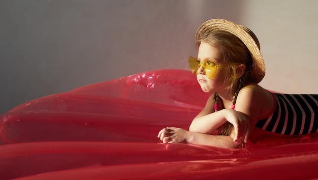 Heureuse petite fille enfant en maillot de bain et un chapeau de paille se prépare pour un voyage d'été à la maison. se trouve sur un matelas pneumatique et rêve d'un été en quarantaine