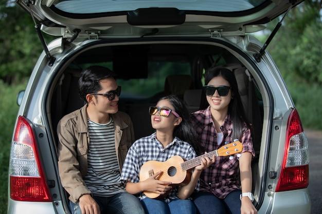 Heureuse petite fille avec la famille asiatique assise dans la voiture