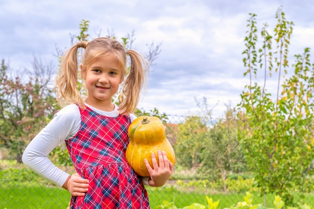 Heureuse petite fille fière vêtue d'une robe de flanelle et tenant une citrouille dans une ferme