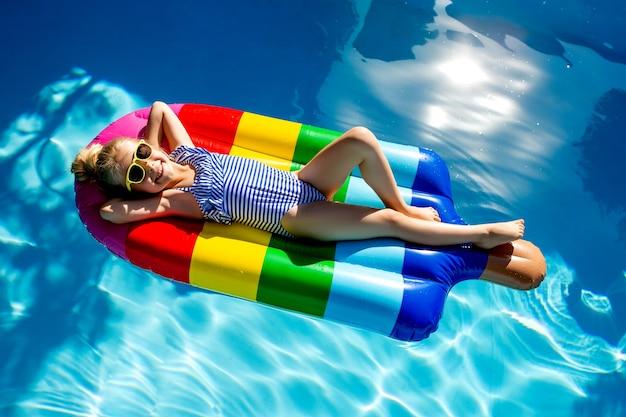 Heureuse petite fille flottant sur un matelas dans la piscine