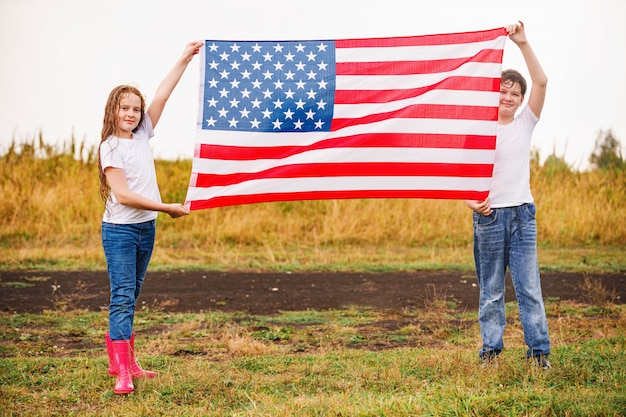 Heureuse petite fille et garçon dans un t-shirt blanc, avec le drapeau américain.