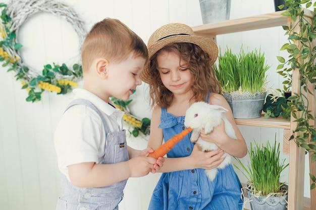 Heureuse petite fille et garçon riant jouant avec un bébé lapin