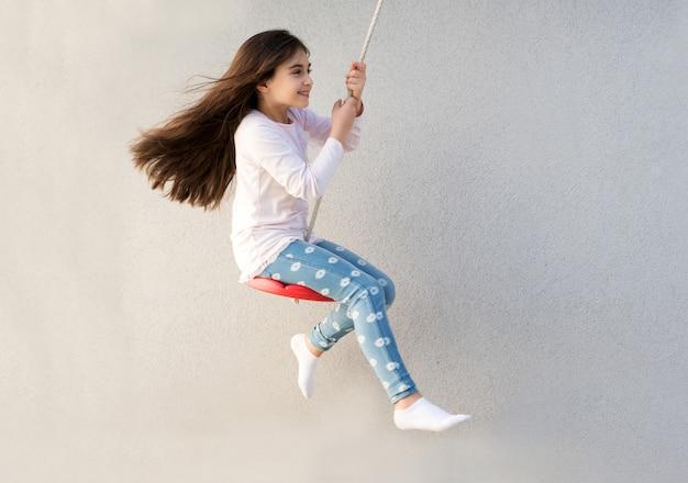 Heureuse petite fille jouant sur une balançoire