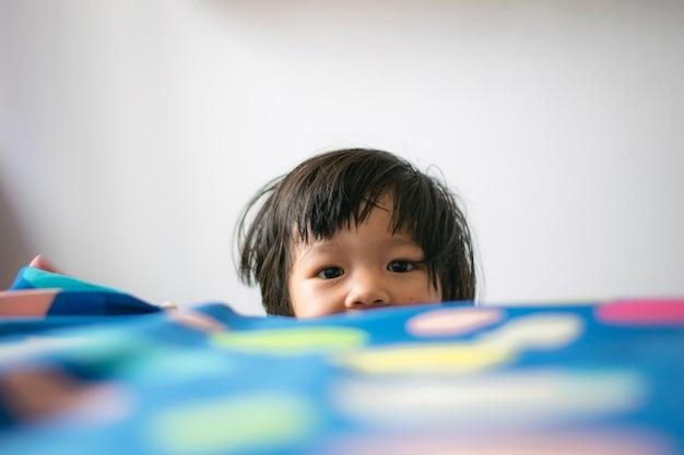 Heureuse petite fille jouant à cache-cache sur le lit