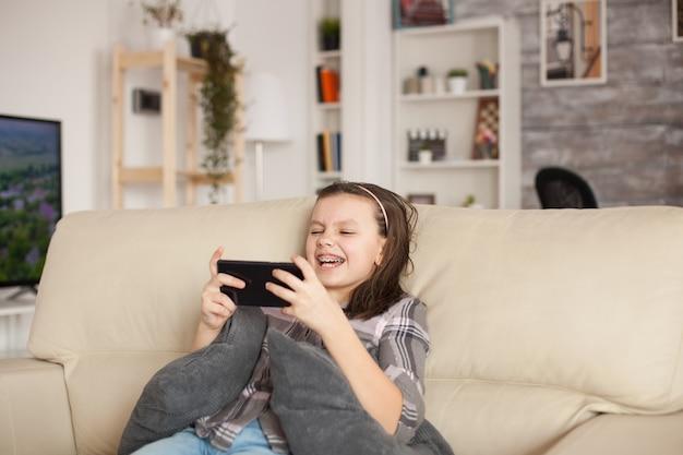 Heureuse petite fille jouant à des jeux sur smartphone assise sur le canapé dans le salon.