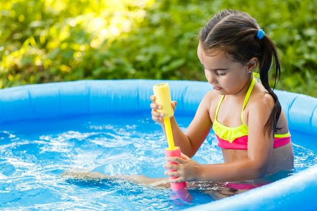 Heureuse petite fille jouant avec une pompe à eau dans une piscine gonflable