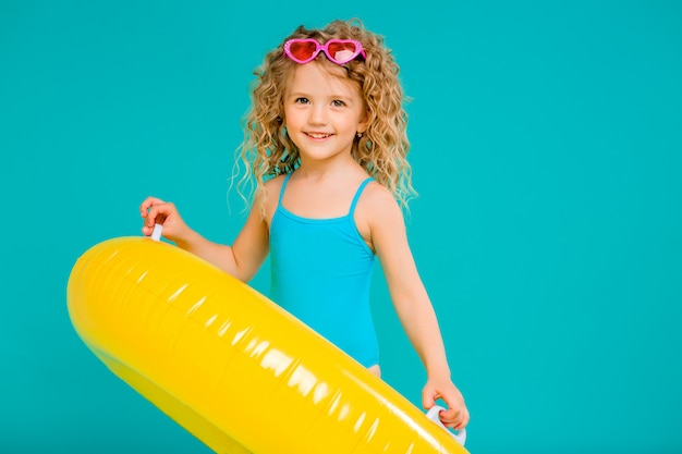 Heureuse petite fille en maillot de bain avec cercle isolé sur fond bleu