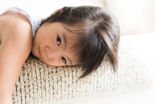 Heureuse petite fille mignonne couchée sur un canapé confortable à la maison.