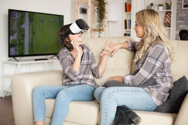 Heureuse petite fille portant un casque de réalité virtuelle assise sur le canapé avec sa mère.