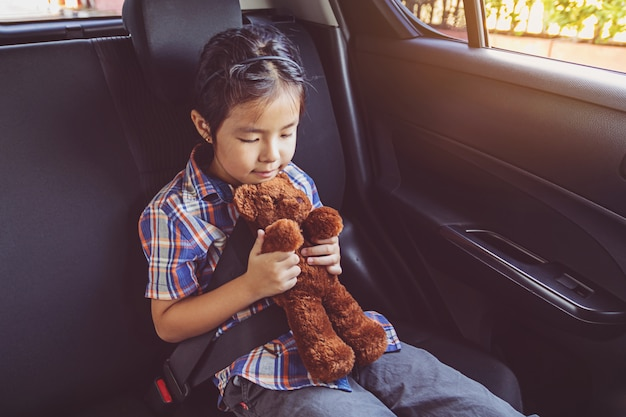 Heureuse petite fille portant la ceinture de sécurité en voiture