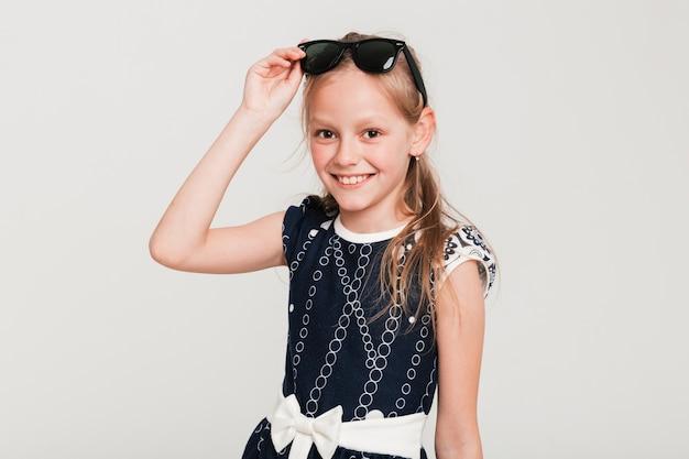 Heureuse petite fille portant des lunettes de soleil