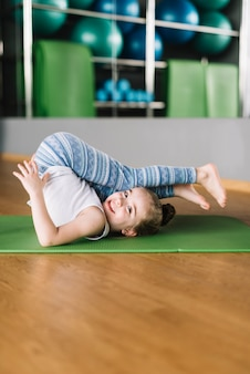 Heureuse petite fille pratiquant le yoga sur tapis en regardant la caméra