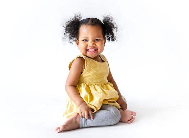 Heureuse petite fille en robe jaune assise