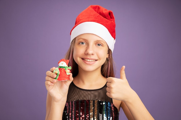 Heureuse petite fille en robe de soirée pailletée et bonnet de noel montrant un jouet de noël regardant la caméra avec le sourire sur le visage montrant les pouces vers le haut debout sur fond violet